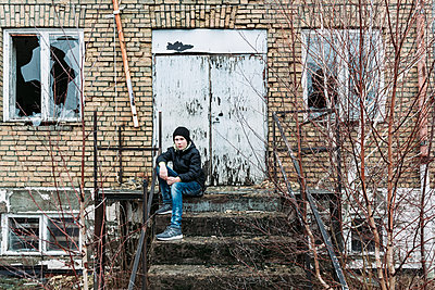 Teenage boy sitting at steps of abandoned building - p312m2092180 by Mikael Svensson
