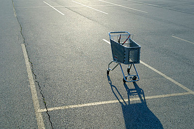 Shopping cart in empty parking lot - p3720419 by James Godman