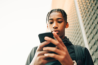 Low angle view of serious teenage boy using mobile phone in city - p426m2074853 by Maskot
