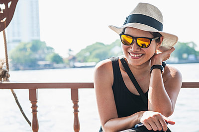 Woman smiling into the camera on a boat on the Chao Phraya river in Bangkok, Thailand - p429m1156282 by Henn Photography