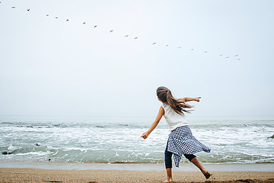 Hispanic girl playing on beach - p555m1409631 by Shestock
