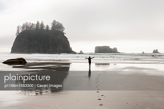 Rear view of silhouette woman with arms outstretched standing at beach in Olympic National Park - p1166m1553300 by Cavan Images