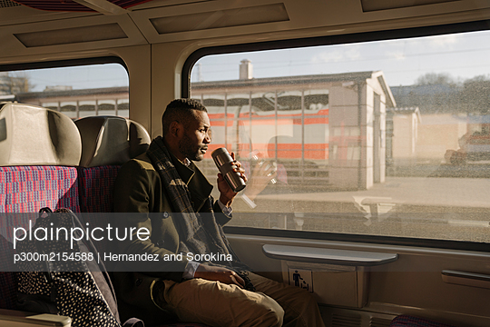 Stylish man drinking hot drink from reusable cup while traveling by train - p300m2154588 by Hernandez and Sorokina