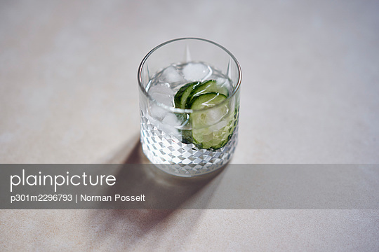 Glass of ice water with cucumber slices - p301m2296793 by Norman Posselt