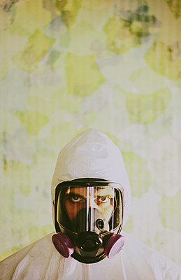 Portrait of a man wearing breathing apparatus and a protective clean suit with a covered head.  - p1100m1112346f by Mint Images