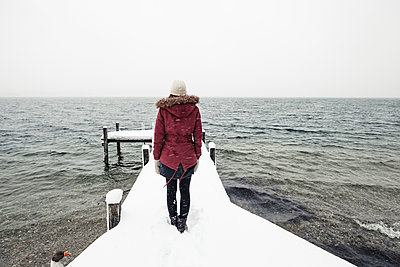 Back view of young woman standing on snow-covered jetty at Lake Starnberg, Germany - p300m2180732 by Wilfried Feder