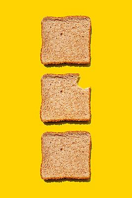 Studio shot of three slices of wheat bread against yellow background - p300m2198255 by Gemma Ferrando