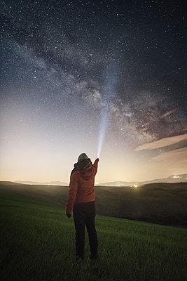 Man shining flashlight at sky at dusk - p343m2002783 by Álvaro Sánchez
