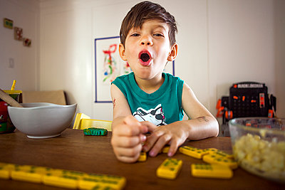 Mixed race boy playing with dominoes at kitchen table - p555m1415461 by Adam Hester