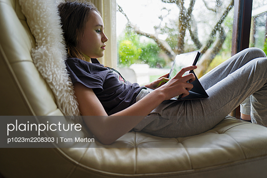 Girl using digital tablet in leather chair - p1023m2208303 by Tom Merton