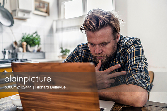 Man using laptop on kitchen table - p300m2132441 by Richárd Bellevue