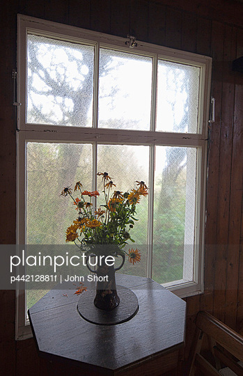 a bouquet of flowers in a vase on a table by the window; northumberland, england