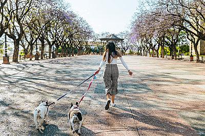 Spain, Andalusia, Jerez de la Frontera, Woman running with two dogs on square - p300m2012692 by Kiko Jimenez