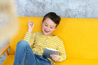 7 year old boy playing with tablet on yellow couch in front of concrete wall - p300m2170330 von Epiximages