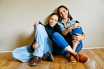 Smiling mixed race women sitting on floor - p555m1523163 by Peathegee Inc