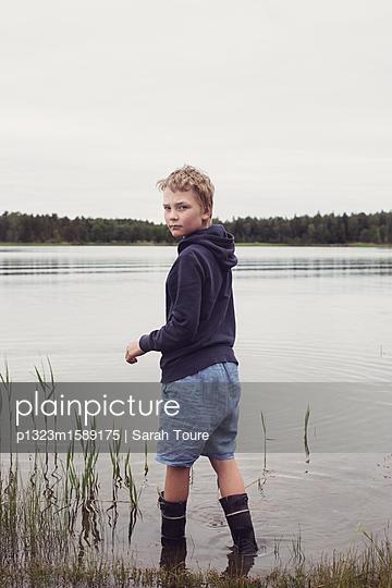 boy by a lake - p1323m1589175 von Sarah Toure