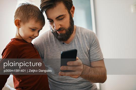 Father explaining little son smartphone - p300m1581401 von Zeljko Dangubic