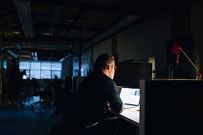 Businessman working late at laptop in dark office - p1192m2095120 by Hero Images