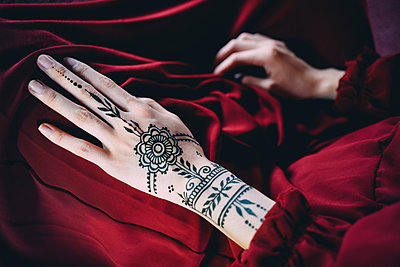 Woman's hand with henna tattoo on red cloth - p300m1587930 von Gemma Ferrando