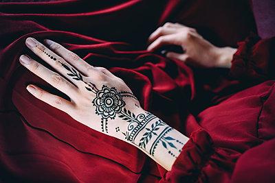 Woman's hand with henna tattoo on red cloth - p300m1587930 von Gemma Ferrando