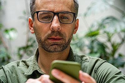 Businessman wearing eyeglasses using mobile phone at cafe - p300m2226706 by Vasily Pindyurin