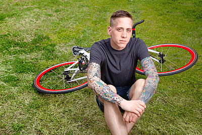 Portrait of young tattooed man sitting on grass - p429m802535 by Cultura