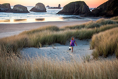 Caucasian girl carrying lantern on beach - p555m1413212 by Adam Hester