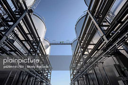 Worker on top of storage tanks in oil blending factory - p429m1417931 by Monty Rakusen