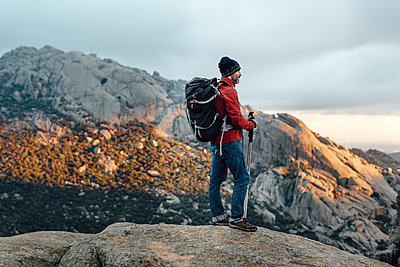Lonely mountain hiker watching rocky scenery at sunset on cloudy day - p1166m2129473 by Cavan Images