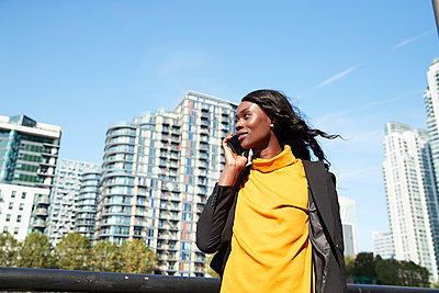 Businesswoman talking on mobile phone in city on sunny day - p300m2241585 by Pete Muller