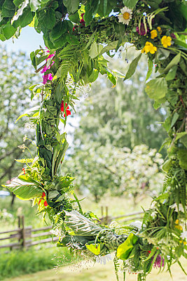 Wreath of flowers hanging on tree - p312m1131280f by Rebecca Wallin