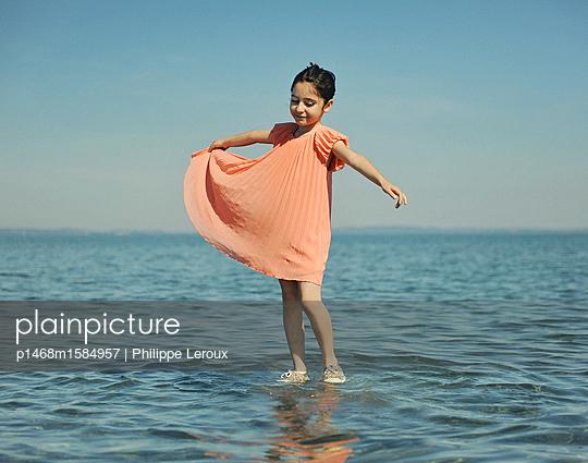 Kleines Mädchen spielt im flachen Wasser - p1468m1584957 von Philippe Leroux