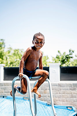 Happy little boy on a ladder of the swimming pool - p300m2121675 by Oscar Carrascosa Martinez