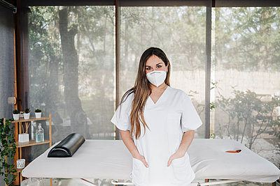 Female doctor with hands in pockets standing in front of massage table in clinic during pandemic - p300m2274165 by Eva Blanco
