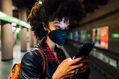 Young woman with face mask using mobile phone at subway - p300m2290771 by Eugenio Marongiu