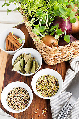 Bowls of various spices lying beside basket with herbs and onions - p312m1548977 by Scandinav Images