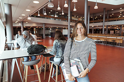 Portrait of female university student standing at cafeteria with friends in background - p426m2072393 by Kentaroo Tryman