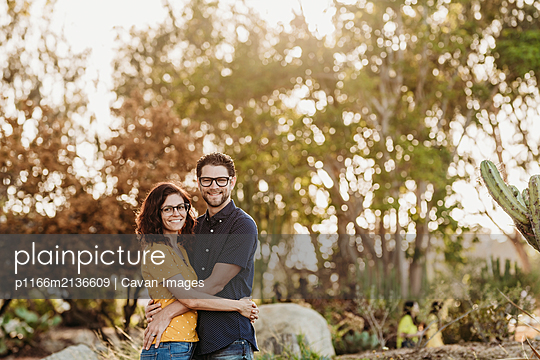 Portrait of husband and wife smiling at camera in sunny cactus garden - p1166m2136609 by Cavan Images