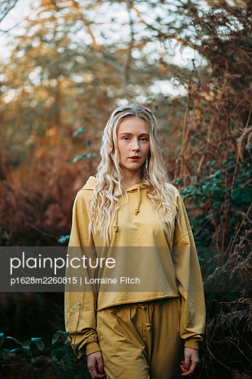 Blonde woman with curly hair and a yellow tracksuit - p1628m2260815 by Lorraine Fitch