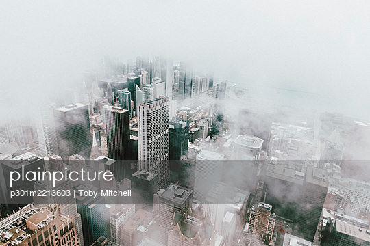 Aerial view highrise buildings in fog, Chicago, Illinois, USA - p301m2213603 by Toby Mitchell