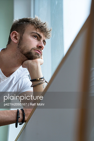Young man looks into the distance - p427m2093167 by Ralf Mohr