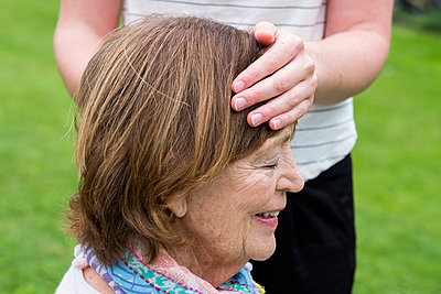 Reiki therapist with a client in a therapy session touching meridian points on the body. - p1100m2220357 by Mint Images