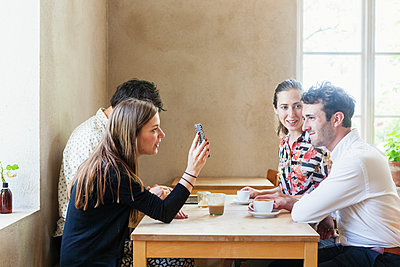 Young colleagues taking coffee break at restaurant - p1264m1066933f by Astrakan