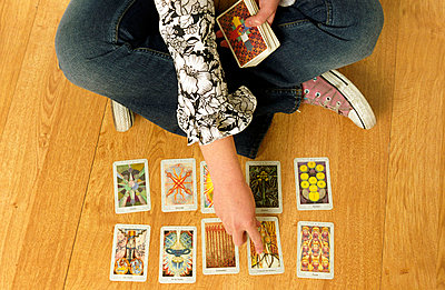 Young woman sitting cross-legged on the floor with tarot cards - p1650168 by Andrea Schoenrock