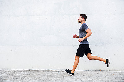 Athlete running in front of white wall - p300m2060639 von Javier Sánchez Mingorance