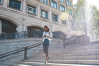 Young businesswoman wearing headphones using mobile phone while walking on staircase in city - p300m2241629 by Pete Muller