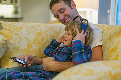 Father with son on his lap as his son listens to music. - p328m840977f by Hero Images
