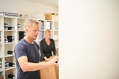 A man and woman, business partners, working together fulfilling orders.  - p429m2190310 by Jakob Helbig