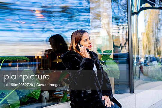 executive woman in the city talking on her smartphone - p1166m2232729 by Cavan Images