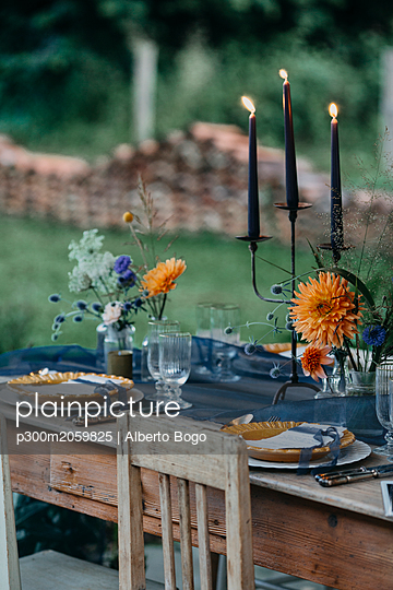 Festive laid table with candles outdoors - p300m2059825 by Alberto Bogo
